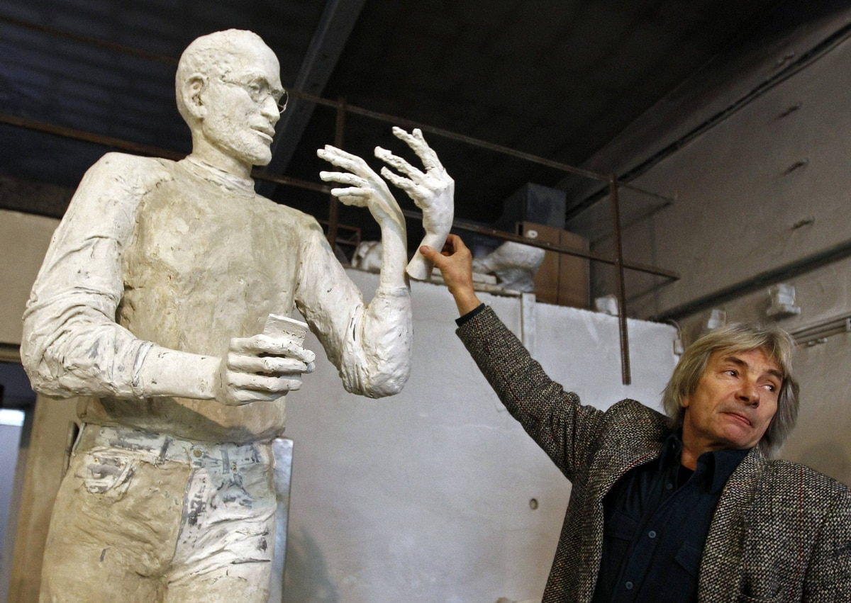 The sculptor tries various hand gestures on a model for the statue. In the other hand, the iconic iPhone. The trademark glasses have been added.