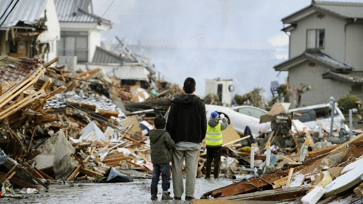 A man and child look out over destroyed homes after a tsunami and earthquake in Sendai, northeastern Japan March 12, 2011.
