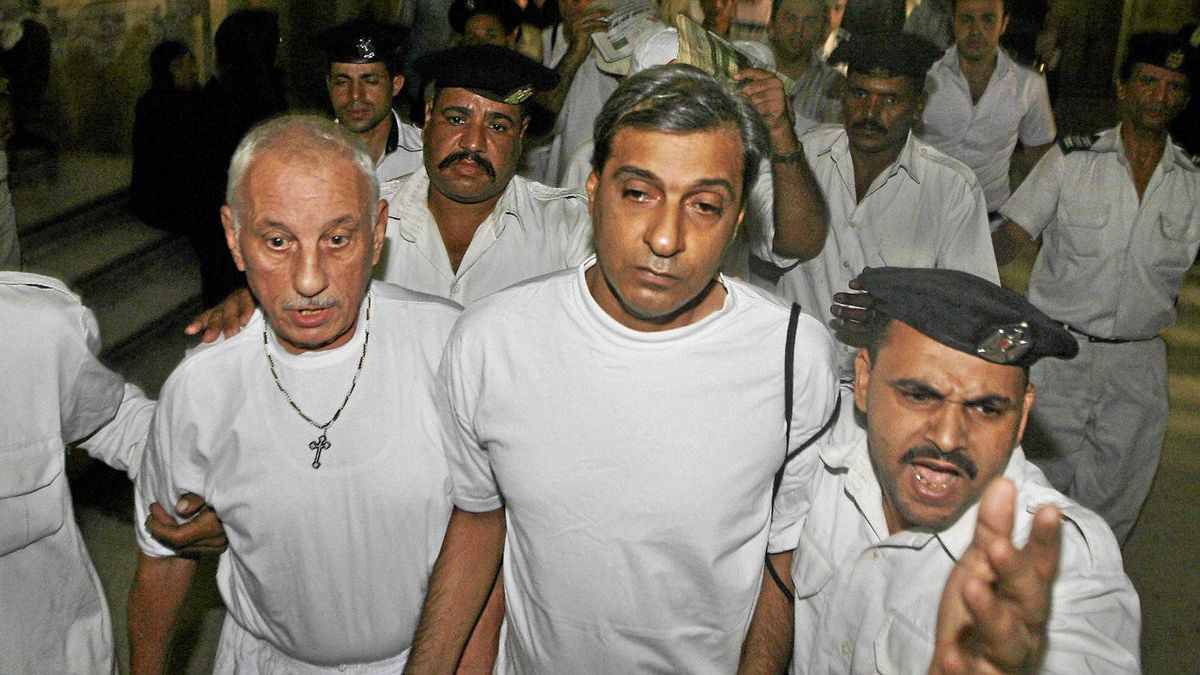 Louis Andraos, left, and Medhat Metyas, centre, U.S. citizens of Egyptian origin accused of trying to illegally adopt Egyptian children, are escorted by police to a courtroom in Cairo on Sept. 17, 2009. Khaled Desouki/AFP/Getty Images