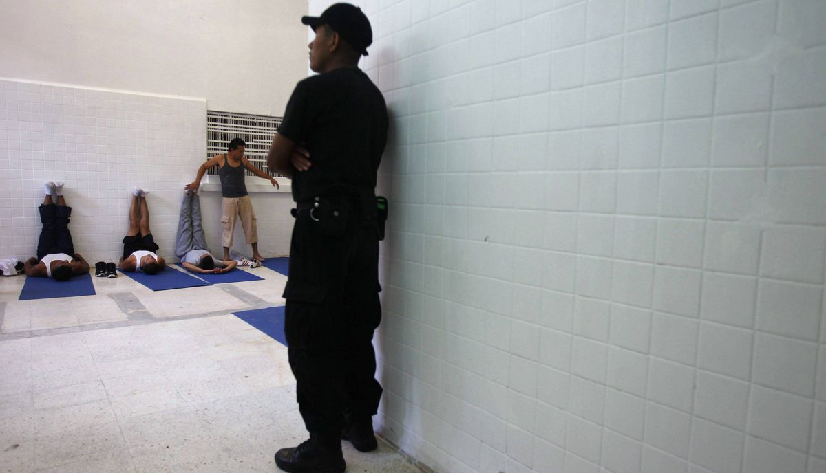 A security guard keeps watch as former inmate and yoga instructor Fredy Diaz Arista teaches yoga inside a juvenile detention centre in Mexico City November 16, 2011.