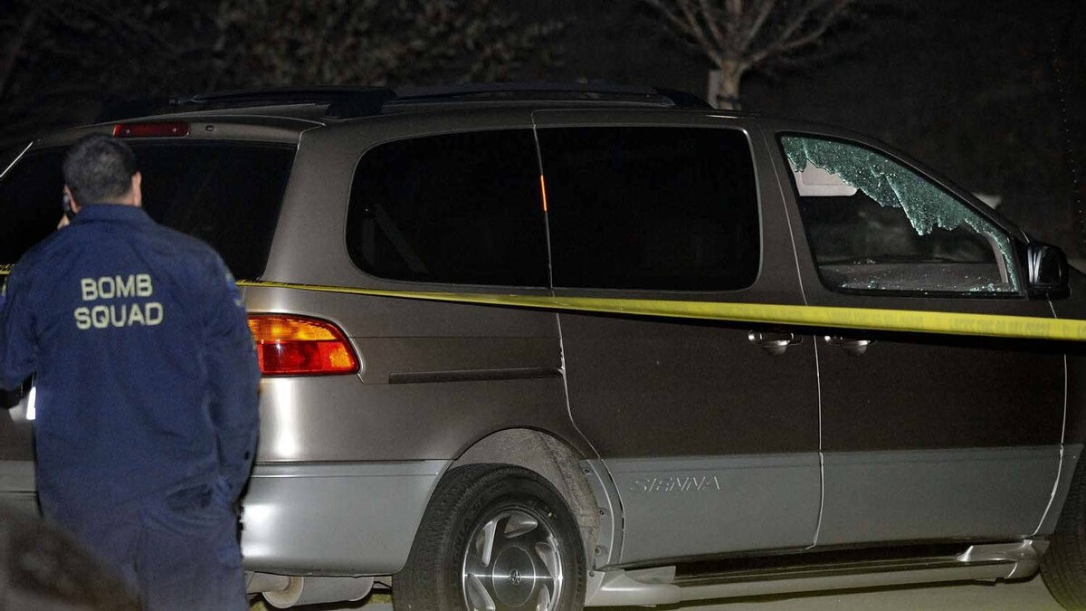 A member of the Alameda County Bomb Squad stands next to the minivan that was hit by the runaway cannonball. The owner of the van told police he and his family had been in the parked van just five minutes before the incident.