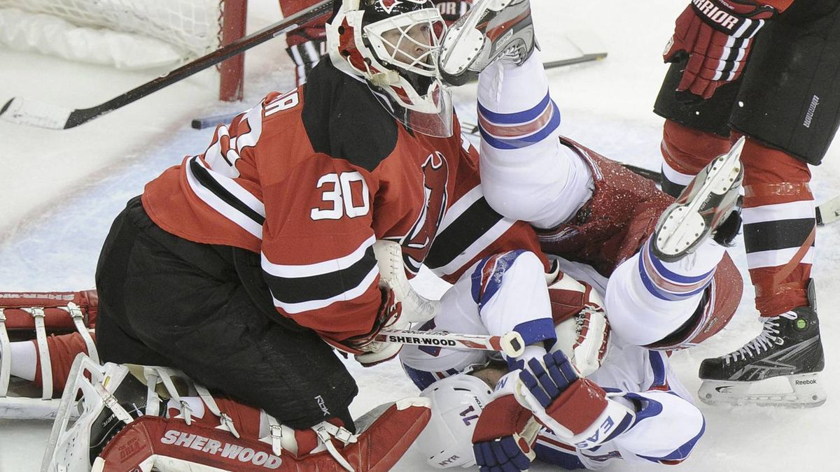 New York Rangers' Mike Rupp (71) flips in front of New Jersey Devils goalie Martin Brodeur during the first period in Game 4 of their NHL Eastern Conference Final hockey playoff game in Newark, New Jersey, May 21, 2012. REUTERS/Ray Stubblebine