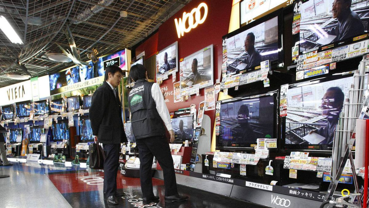 In this Feb. 3, 2010 file photo, a shopper listens to a salesclerk in front of flat-panel TVs at an electronics store in Tokyo. Japan's economy stumbled in the last three months of the year, contracting for the first time in five quarters. Gross domestic product shrunk at an annualized rate of 1.1 percent in the October-December period, the government said Monday Feb. 14, 2011.