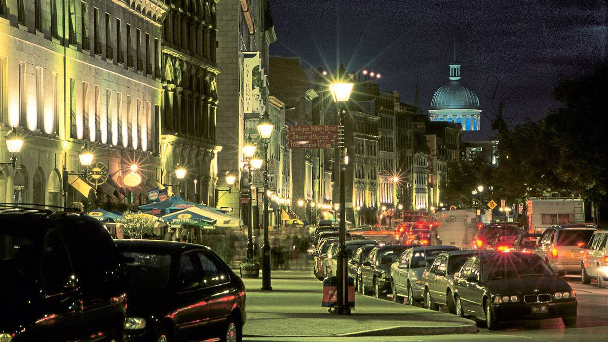 Old Montreal's De la Commune Street at night, with the dome of Bonsecours Market in the distance.