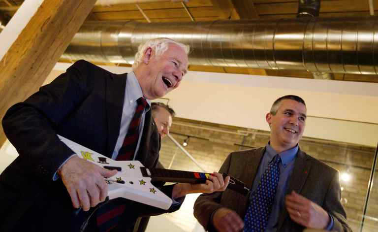 Governor-General David Johnston uses a guitar-shaped game controller to play an educational science game during a visit to Spongelab Interactive in Toronto on March 14, 2012. He is being assisted by Ed Hitchcock, who is a teacher in Toronto.