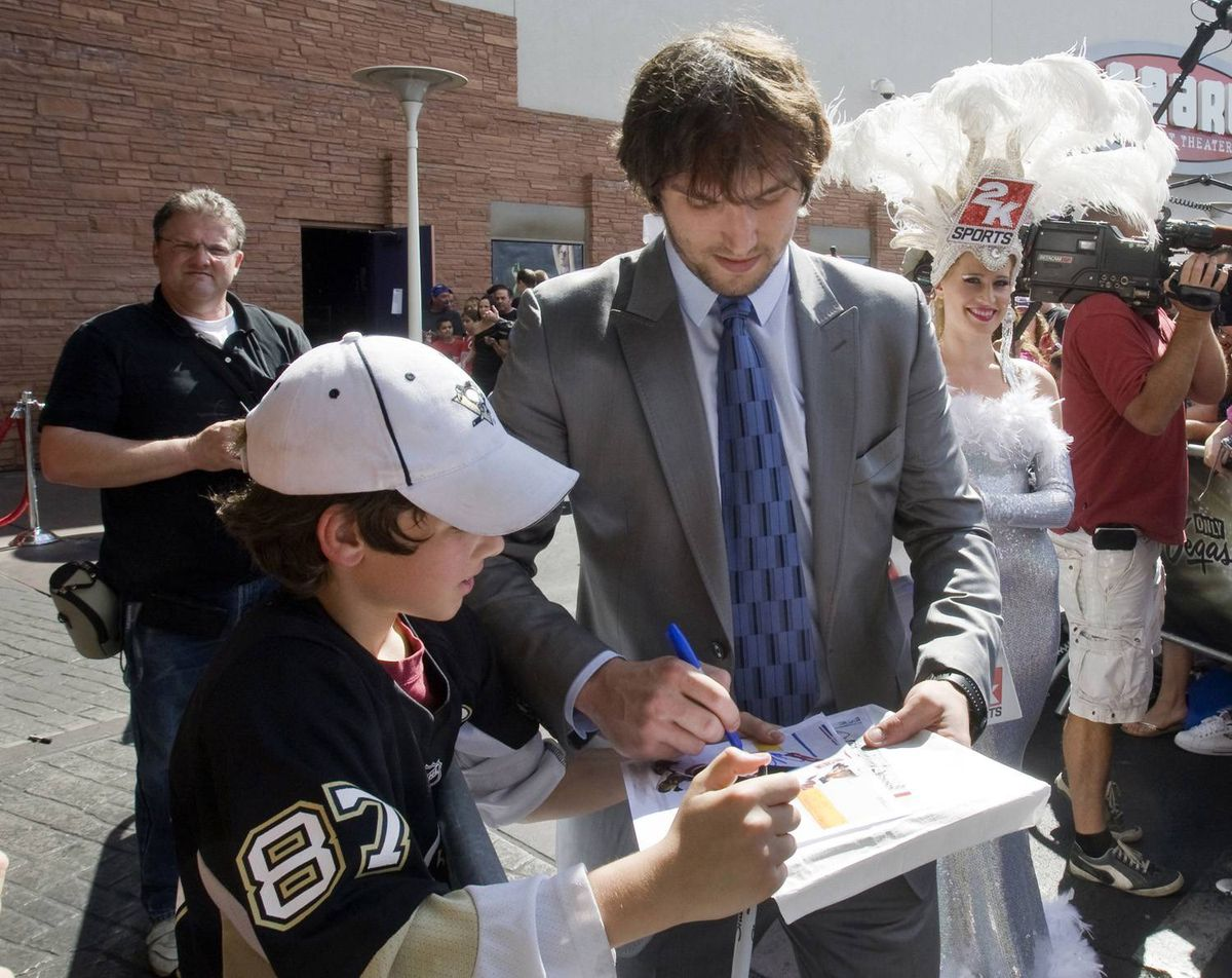 Washington Capitals winger Alex Ovechkin signs autographs for a Sidney Crosby fan.