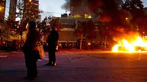 Riot officers keep a perimeter around two burning police cars in downtown Vancouver June 15, 2011 during the Stanley Cup riot. John Lehmann/The Globe and Mail
