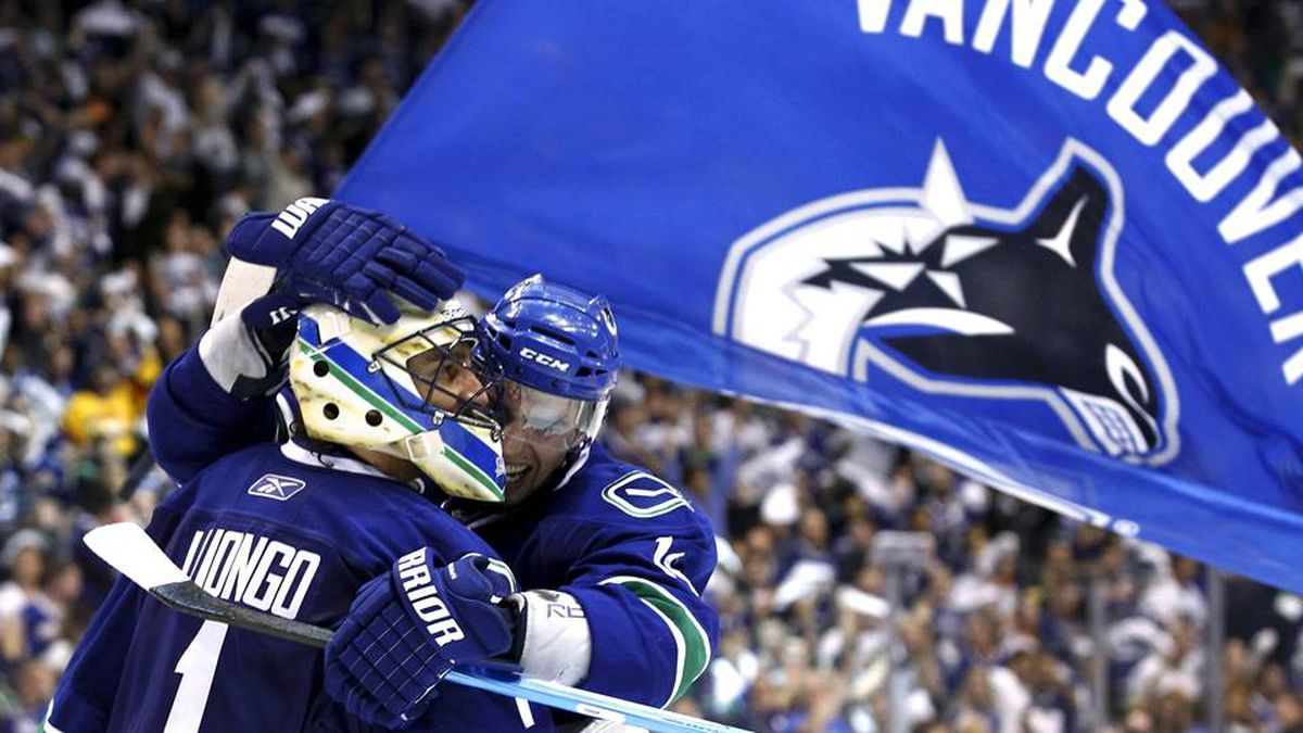 Vancouver Canucks goalie Roberto Luongo and forward Alex Burrows celebrate after defeating the Boston Bruins in Game 5.