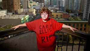 Lori-Ann Ellis wears a memorial t-shirt remembering her slain sister-in-law Cara Ellis as she stands on the balcony of her Vancouver hotel room Oct. 14, 2011.