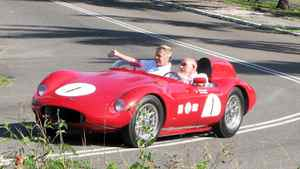 Sir Stirling and Lady Moss navigate a tight right-hander on the hillclimb course in their beautifully restored 1.5 litre, OSCA sports car. Moss won the 12 hours of Sebring in a similar car in 1954.