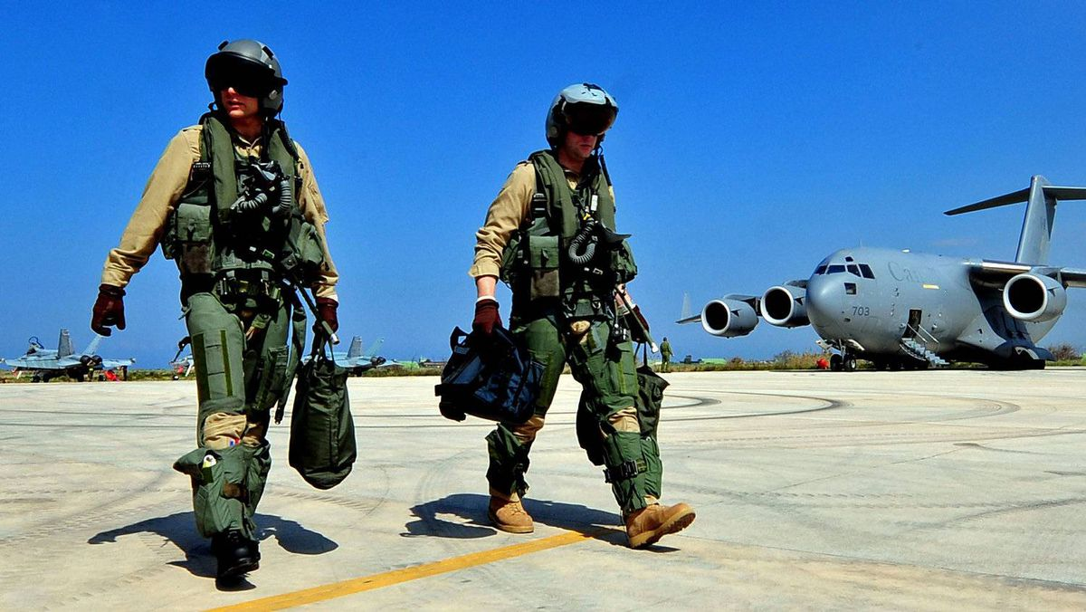 Canadians pilots walk across the tarmac at Trapani airbase in Italy on March 24, 2011, after flying a mission over Libya.