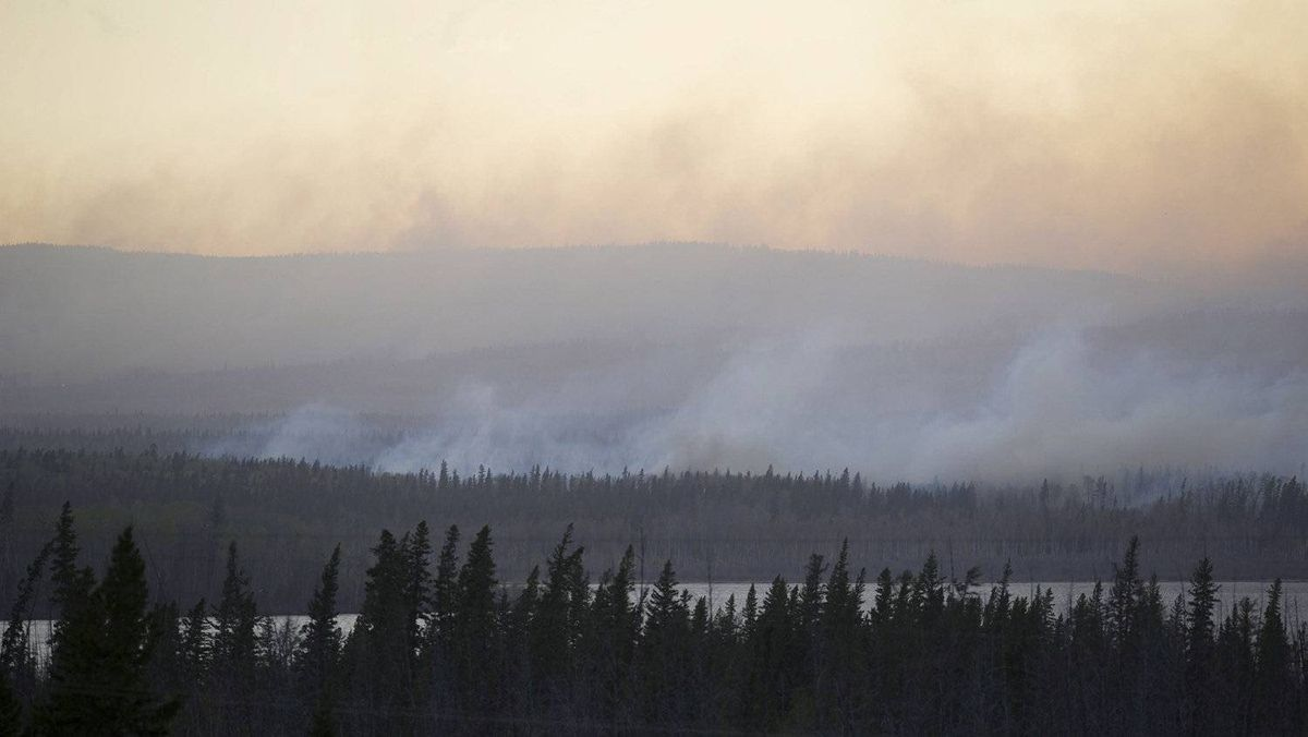 White smoke rises around Slave Lake, 300 km northeast of Edmonton, Alberta, on Sunday May 15, 2011. Over a thousand people were ordered to leave their homes on Sunday when strong winds fanned two separate wildfires that burned on either side of a northern Alberta town.