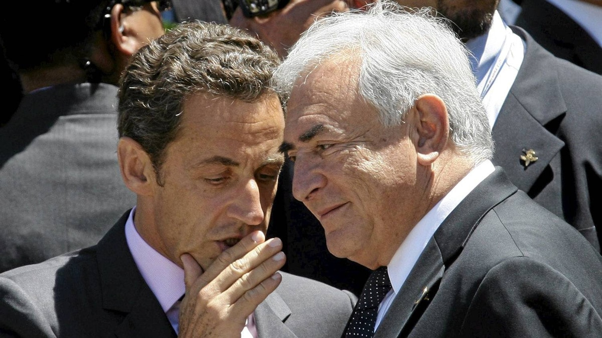 International Monetary Fund Managing Director Dominique Strauss-Kahn (R) speaks with France's President Nicolas Sarkozy before a family photo during the G8 summit in L'Aquila, Italy July 9, 2009.