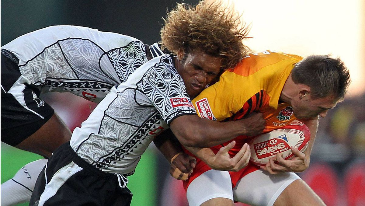 Christian Lewis -Pratt England (R) is tackled by Osea Kolinisau of Fiji (C) during their Dubai Rugby Sevens World Series semi-final match in the Gulf emirate of Dubai on December 3, 2011. England won 19-12. Getty Images/KARIM SAHIB