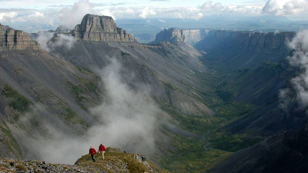 People walk on a cliff overlooking Ram Plateau in the Nahanni National Park Reserve, Northwest Territories in this undated handout photo released June 9, 2009.