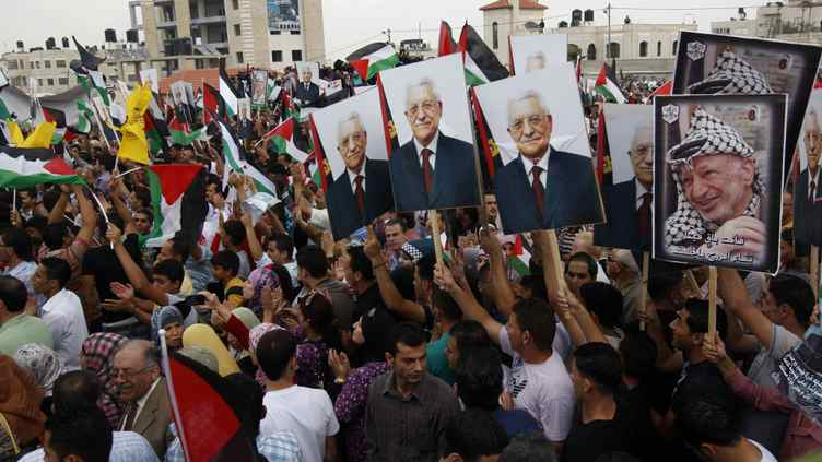 Thousands of cheering Palestinians welcome their president Mahmud Abbas (poster) outside his Ramallah headquarters on Sept. 25, 2011, as he returned from delivering a historic UN membership bid.