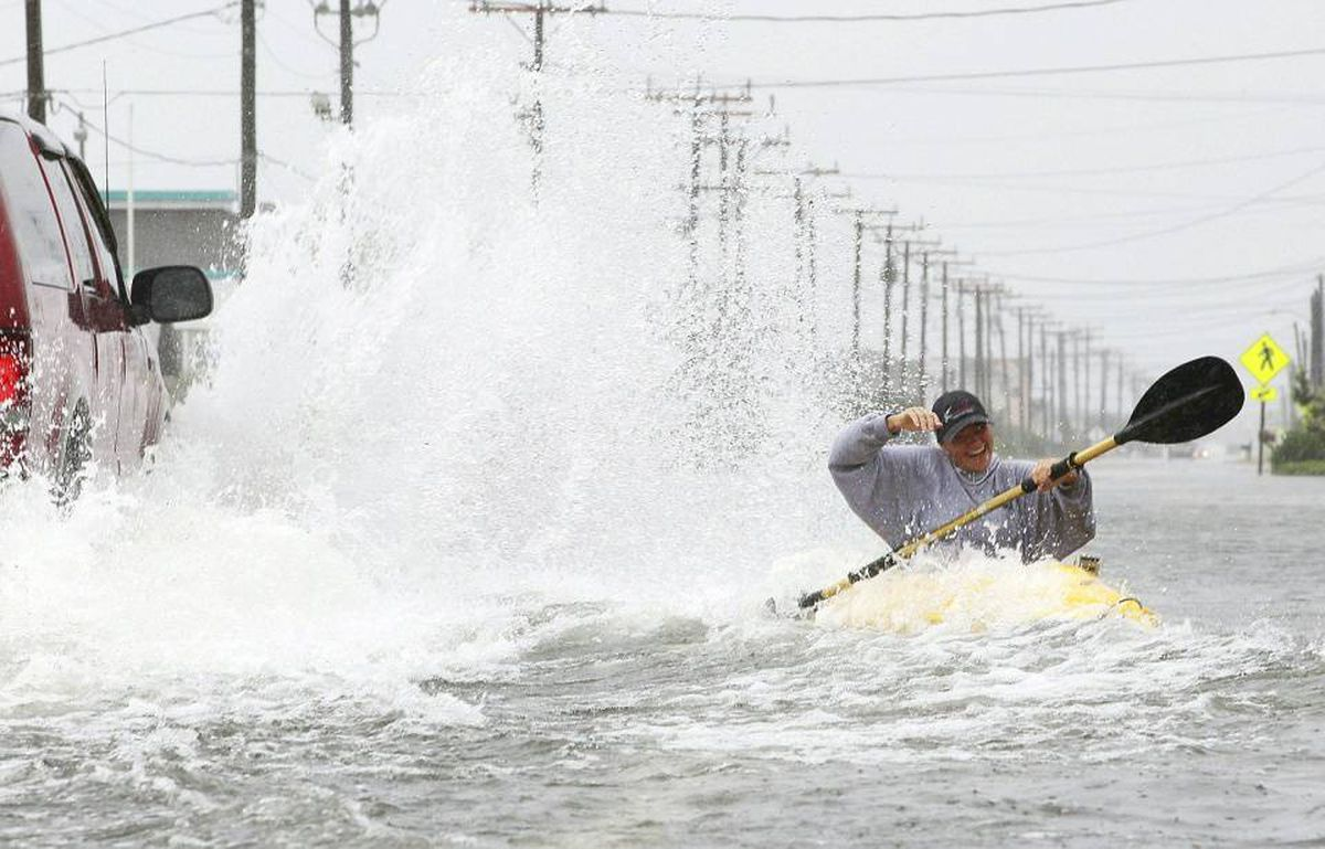 Kellie Maier gets splashed by a passing car while kayaking on water covered Highway 12, on September 3, 2010 in Kill Devil Hills, North Carolina. Hurricane Earl was downgraded to a category 2 before brushing the Outer Banks early Friday morning causing minimal damage.
