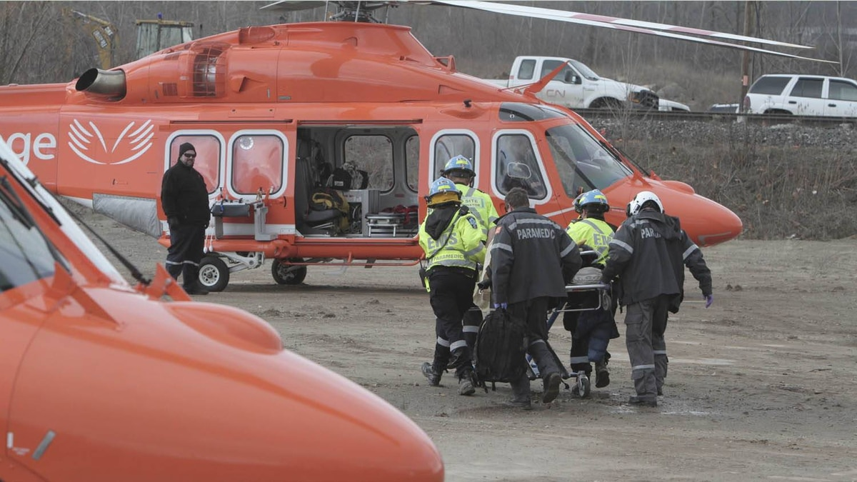 Rescue workers on the scene of a derailed Via train in Burlington rush an injured passenger to a helicopter Sunday February 26, 2012.