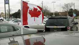 A Canadian flag flies from the window of a General Motors vehicle at a car dealership in Toronto