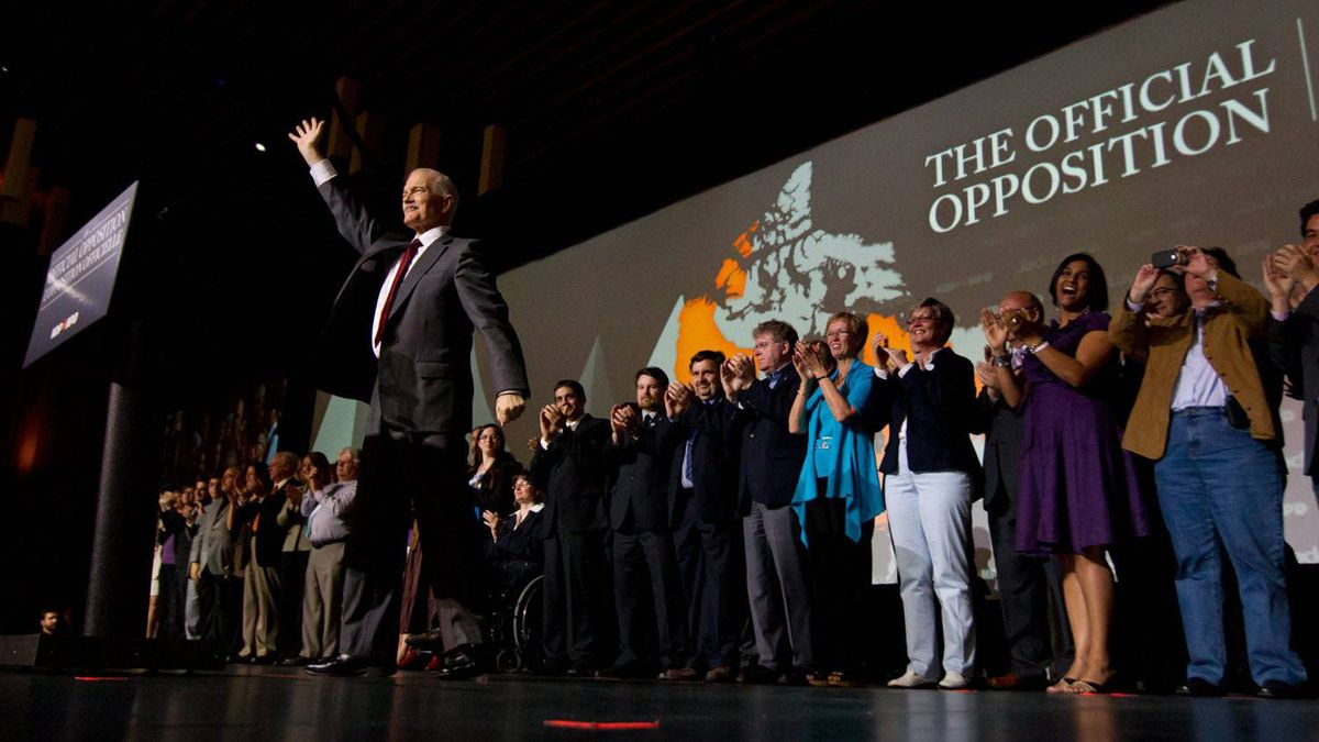 NDP leader Jack Layton is flanked by his fellow MP's as he waves after delivering a speech to open the party's 50th anniversary convention in Vancouver, B.C., on Friday June 17, 2011.