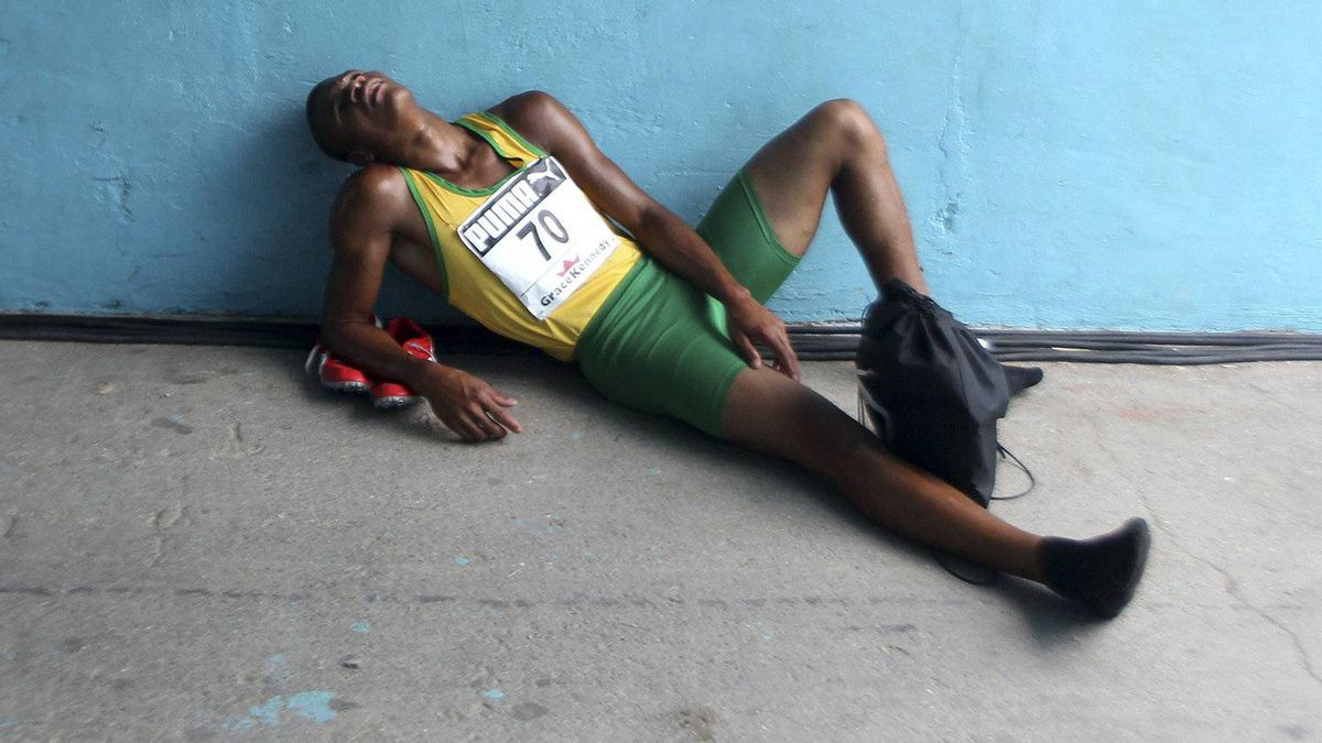 An athlete rests after his race at the Jamaica's Inter-Secondary Schools Boys and Girls Athletics Championships in Kingston March 29, 2012. REUTERS/Ivan Alvarado (JAMAICA - Tags: SPORT ATHLETICS)