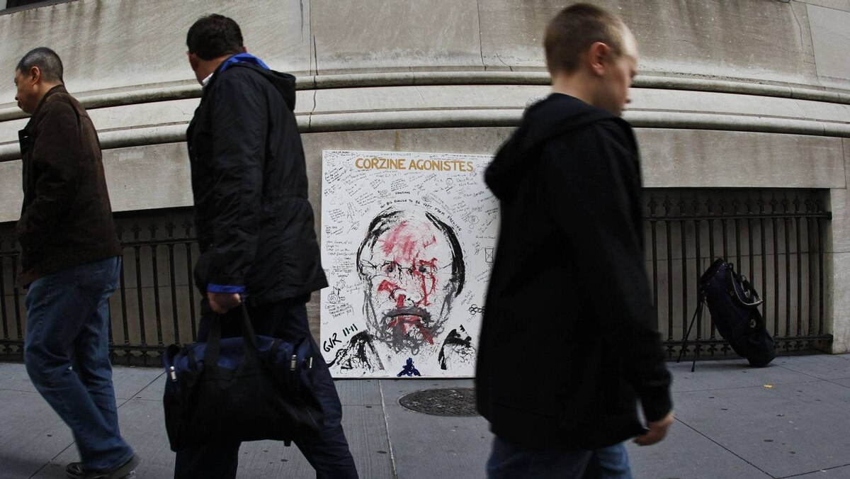 Pedestrians pass a portrait of former MF Global chief John Corzine across from the New York Stock Exchange.