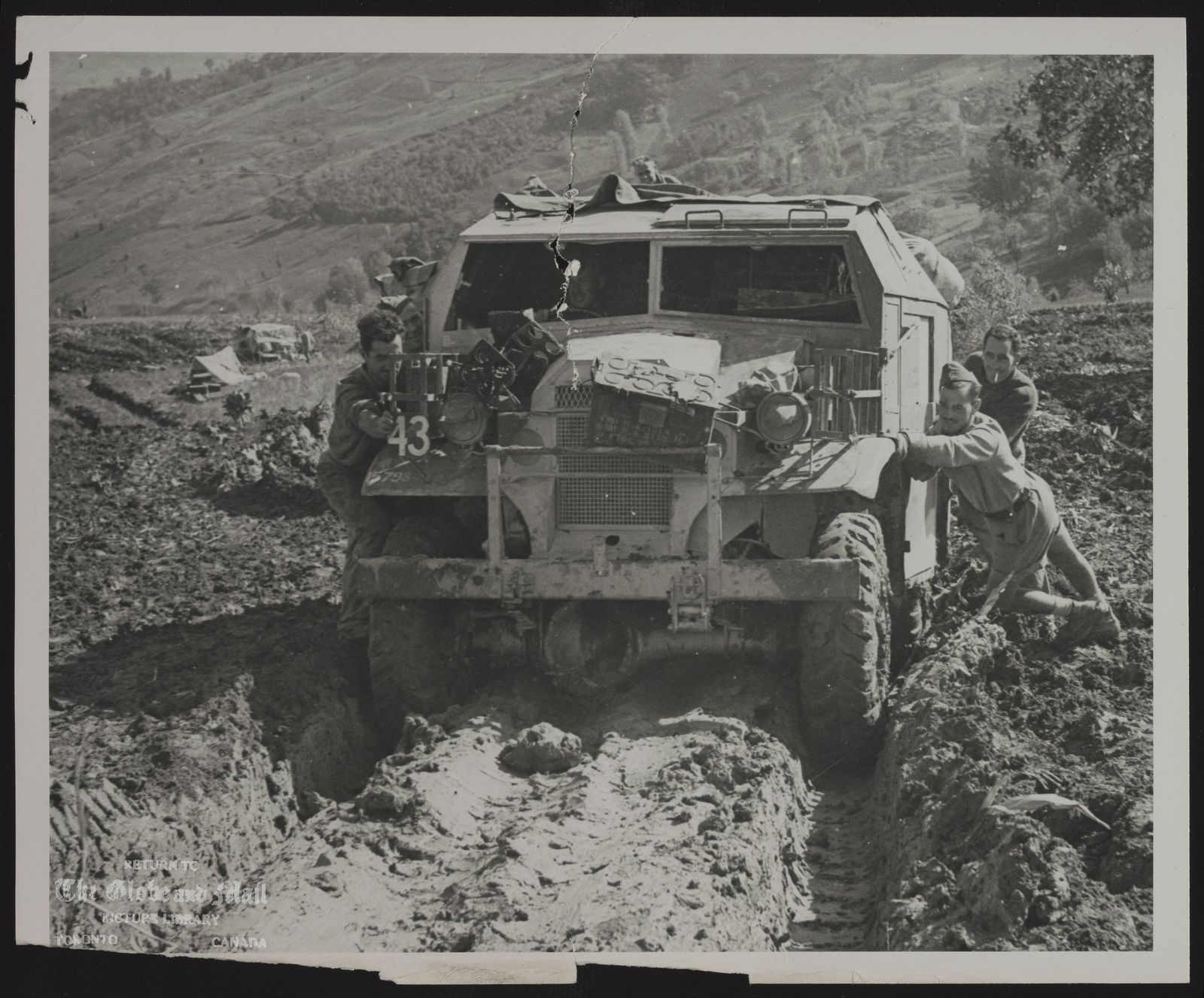 WORLD WAR II Canada Forces in Italy (ADVANCE) MEN AND MACHINE—Men of the 10th Field Battery, 4th Canadian Division, help field artillery tractor plow through muddy fields during the Allied advance in Italy during the Second World War. This scene is near Torella on Oct. 30, 1943, less than two months after the Allies landed in Italy 20 years ago. (CP Photo from National Defence)