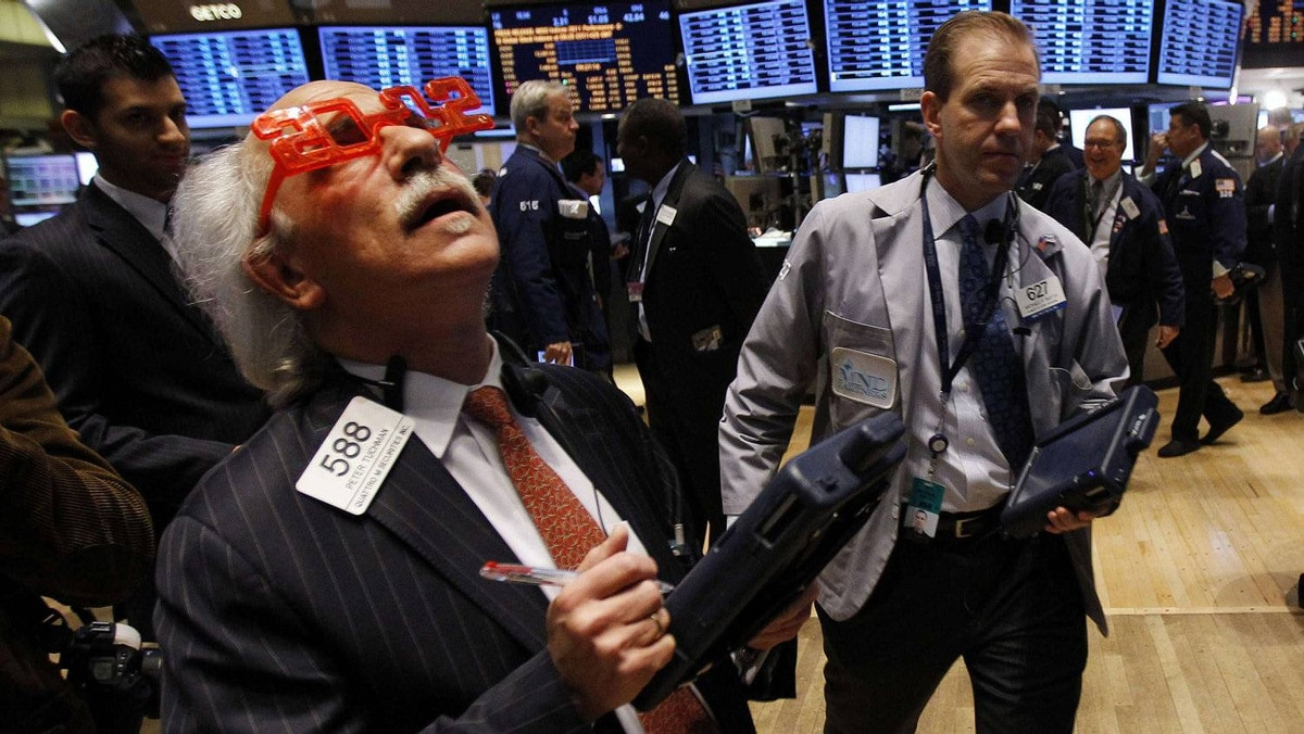 """Trader Peter Tuchman of Quattro M Securities Inc. wears """"2012"""" glasses as he works on the main trading floor of the New York Stock Exchange during the final trading day of 2011 in New York December 30, 2011."""