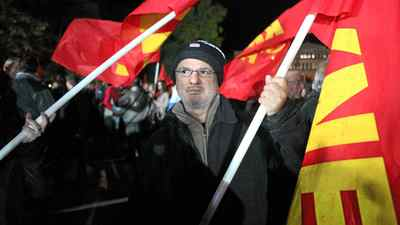 "Yanis Tsakalos, 51, carries a Communist flag at a rally in front of the Greek Parliament on Friday night. His wife lost her job as a sales clerk five days ago, he said, and his own work as a street sweeper seems increasingly at risk because of downsizing by the municipal government. His salary has been cut in half in the last two years, he said, and he can no longer afford to buy fuel for the central heating system in their home. ""We get under a pile of blankets and use the fireplace,"" he said."
