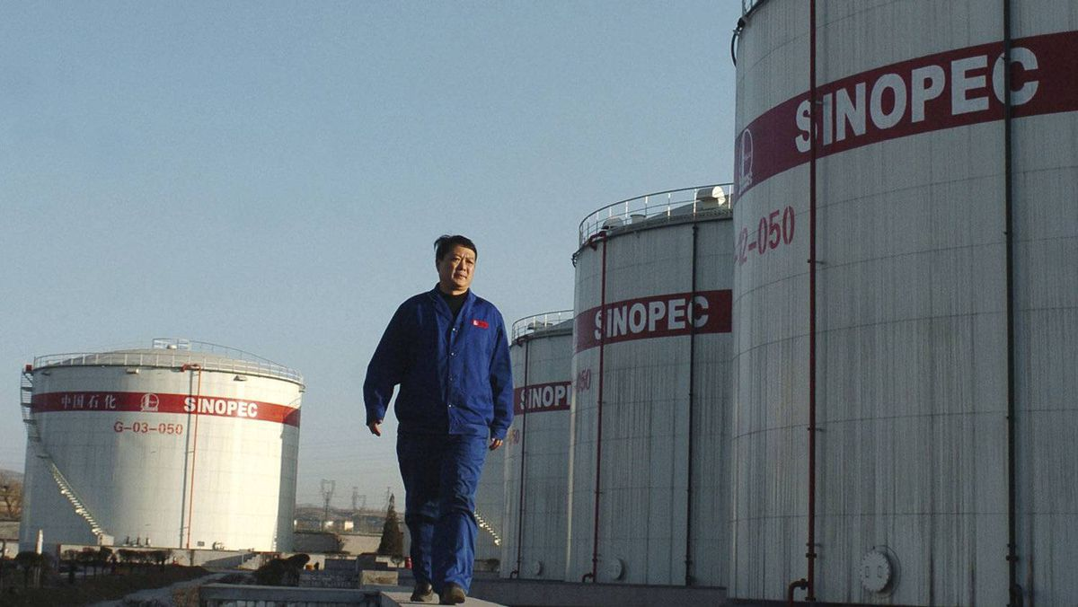 An employee walks at an oil storage site of the Sinopec Corp. on the outskirts of Taiyuan, the capital of north China's Shanxi province, Nov. 19, 2007.
