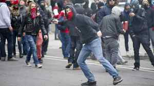 A demonstrator throws a rock towards the police line during a student demonstration outside the Montreal Convention Centre against hikes to university and college tuition fees Friday, April 20, 2012 in Montreal.