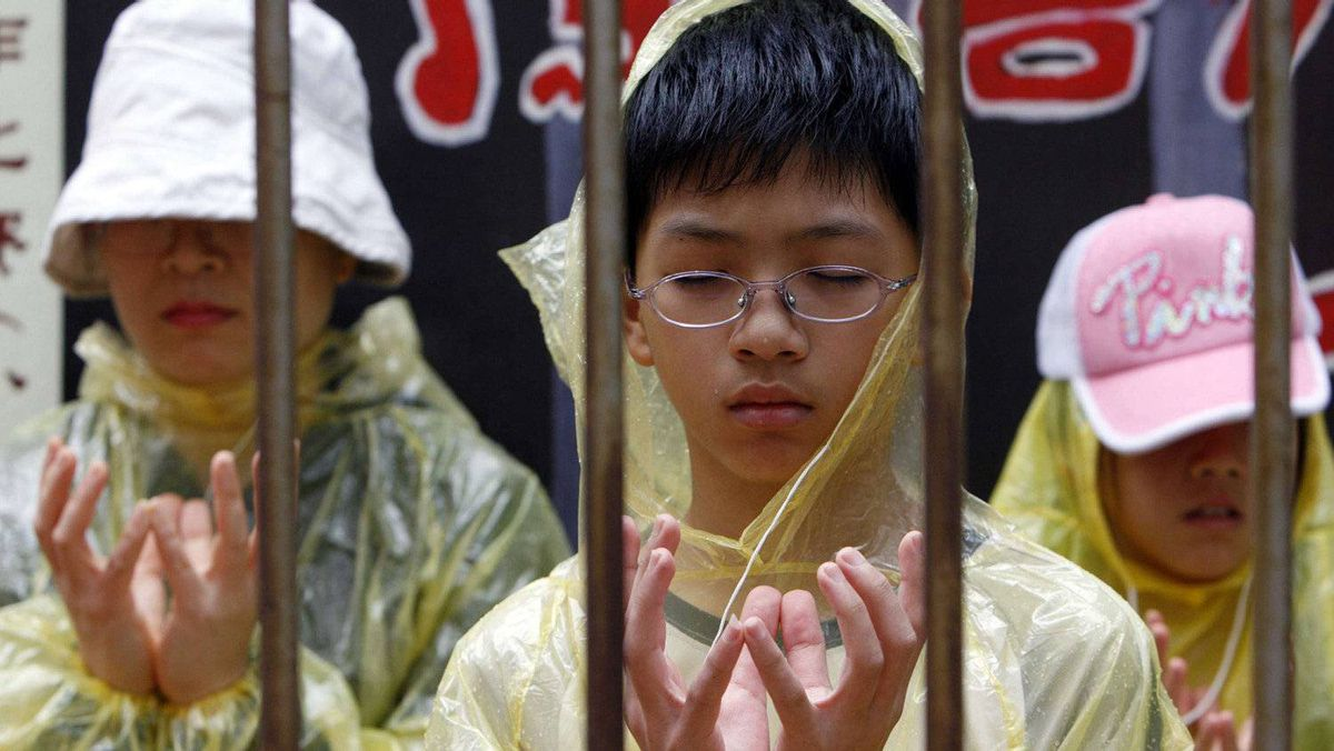Falun Gong members meditate during a demonstration outside the Chinese government's local liaison office in Hong Kong June 30, 2007.