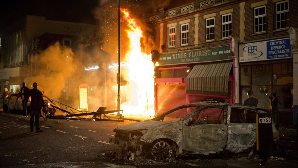 A shop and police car burn as riot police try to contain a large group of people on a main road in Tottenham, north London on August 6, 2011.