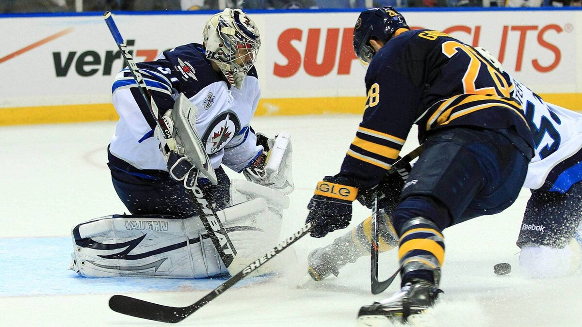 Winnipeg Jets goalie Ondrej Pavelec (31) stops a shot by Buffalo Sabres center Paul Gaustad (28) during the second period at the First Niagara Center.