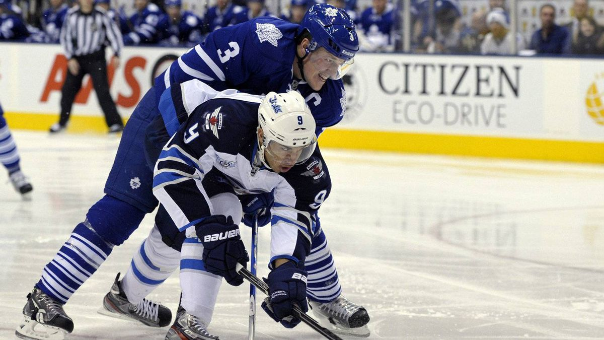 Toronto Maple Leafs defenceman Dion Phaneuf checks Winnipeg Jets forward Evander Kane in the first period.