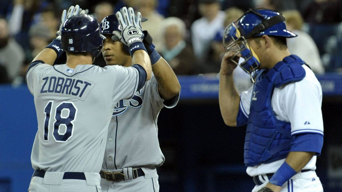 Tampa Bay Rays batter Ben Zobrist celebrates his two-run home run with Desmond Jennings (C) in front of Toronto Blue Jays catcher Jeff Mathis (R) during the first inning of their MLB American League baseball game in Toronto April 18, 2012.