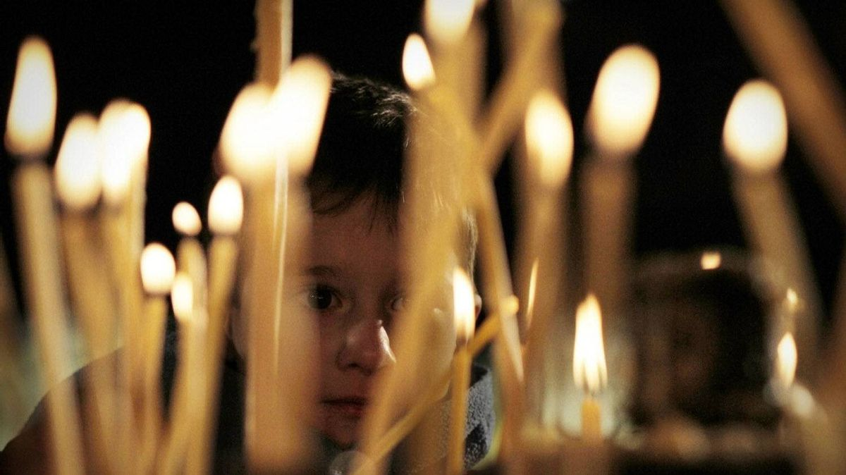 A child lights candle during the traditional Christmas mass at the golden domed Alexander Nevsky cathedral in downtown Sofia, Sunday, Dec. 25, 2011.