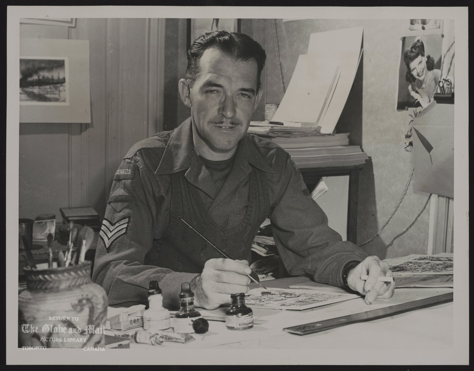 The notes transcribed from the back of this photograph are as follows: W.G. (Bing) COUGHLIN FAMOUS CANADIAN ARMY CARTOONIST DRAWS ANOTHER GEM Sgt. W.G.