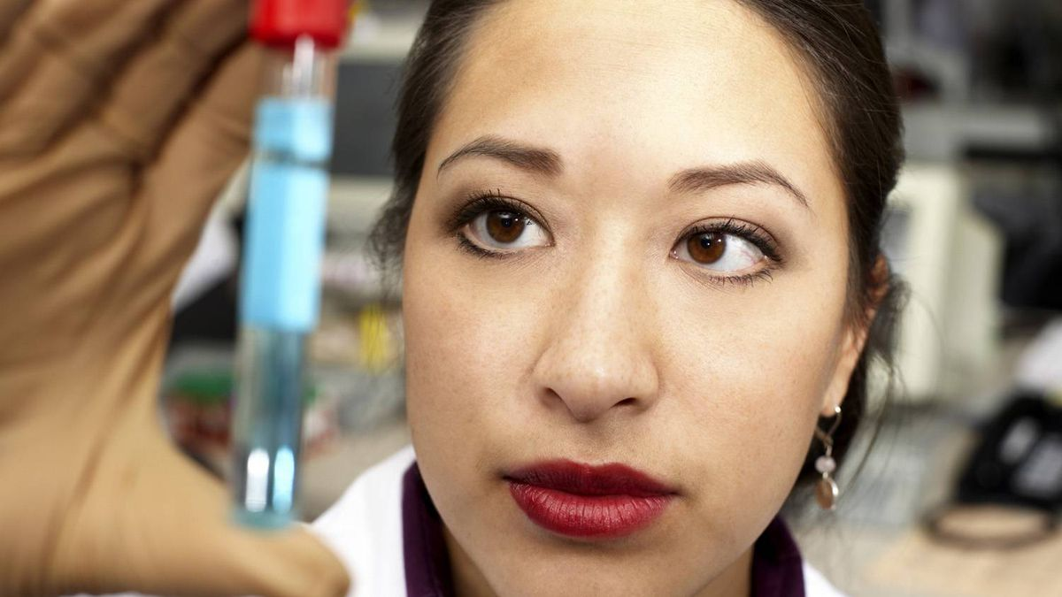 A scientist holds up a test tube.