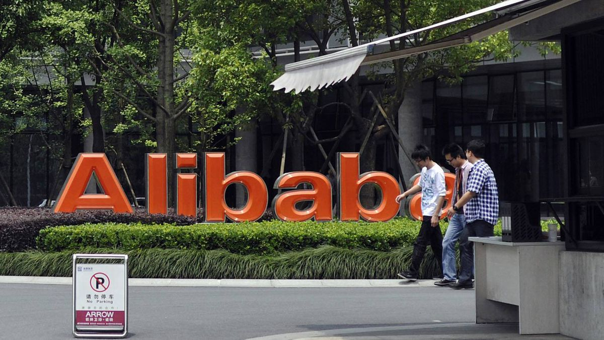 Young men walk past the corporate logo at the headquarters compound of Alibaba Group in Hangzhou in eastern China's Zhejiang province Monday May 21, 2012.