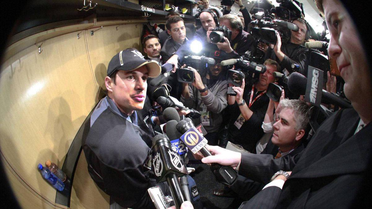 Pittsburgh Penguins' Sidney Crosby, left, is surrounded by media at his locker after a morning skate in preparation for his return to NHL hockey action against the New York Islanders in Pittsburgh, Monday, Nov. 21, 2011. Crosby will play in his first game in nearly a year since being sidelined with concussion-like symptoms. (AP Photo/Gene J. Puskar)