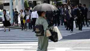 """A woman in a traditional """"Kimono"""" carries shopping bags at a shopping district."""