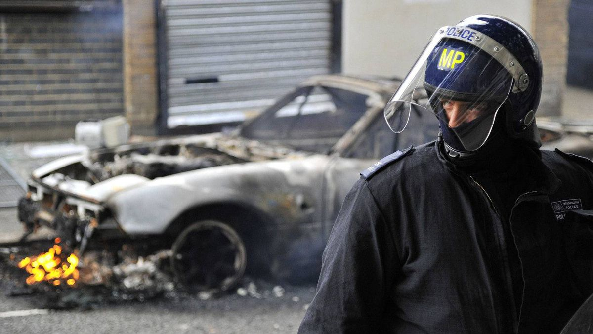A police officer in riot gear stands in front of a burning car on a street in Hackney, east London.