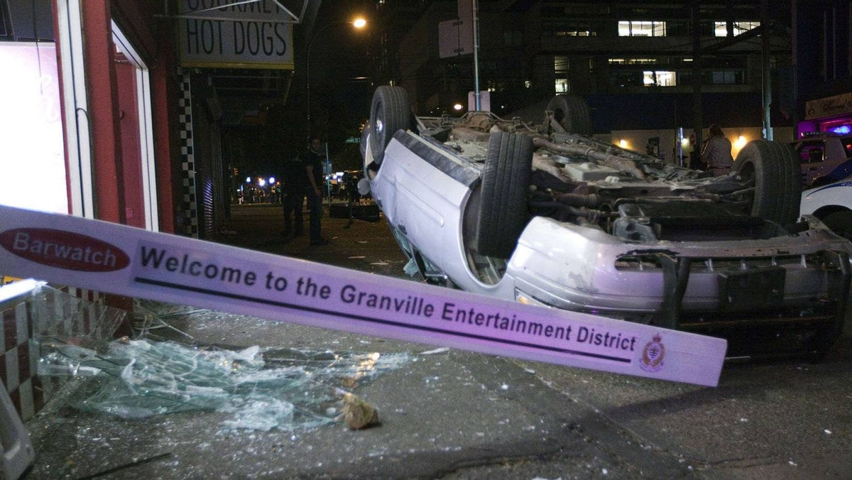 An overturned car sits on a Vancouver sidewalk after riots following the Canucks? Game 7 loss to the Boston Bruins.