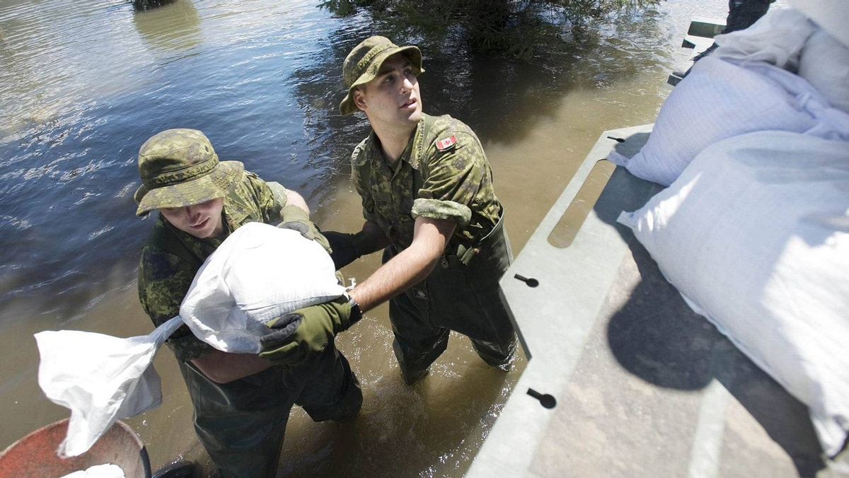 Canadian armed forces personnel unload sandbags at a house immersed in flood waters in the town of Saint-Blaise-Sur-Richelieu, Que., Sunday, May 8, 2011.