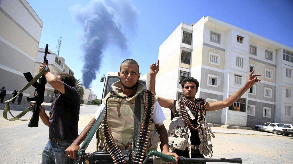 Libyan rebel fighters react as they search for snipers while fighting for the final push to flush out Moammar Gadhafi's forces in Abu Slim area in Tripoli August 25, 2011.