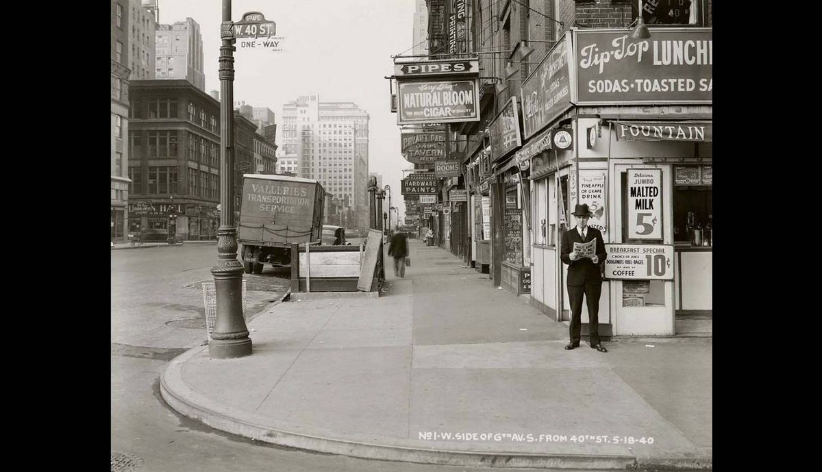 """In this May 18, 1940 photo provided by the New York City Municipal Archives, a man reads a newspaper on New York's 6th Ave. and 40th St, with the headline: """"Nazi Army Now 75 Miles From Paris."""""""