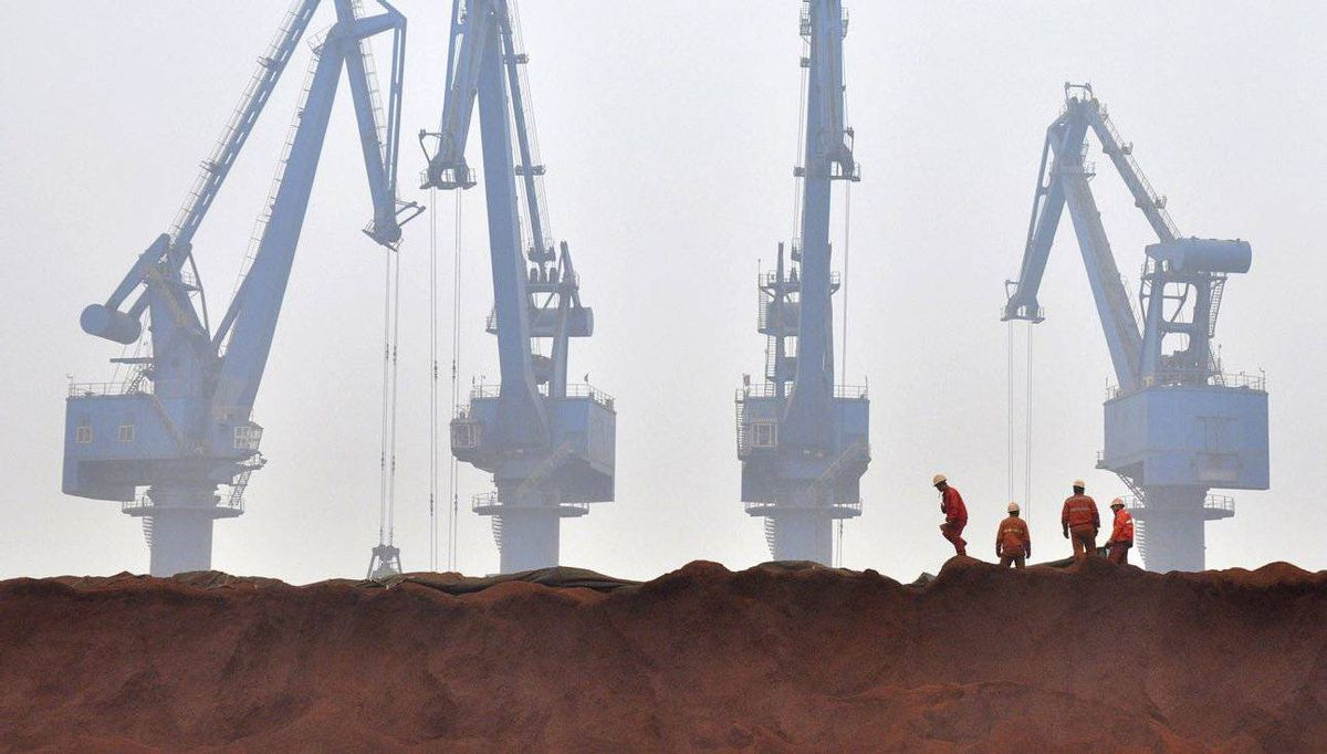 Workers remove the covering from Australian iron ore at the port in Tianjin municipality in China.