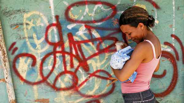 A woman feeds her child as she waits for transportation in Las Mayas.