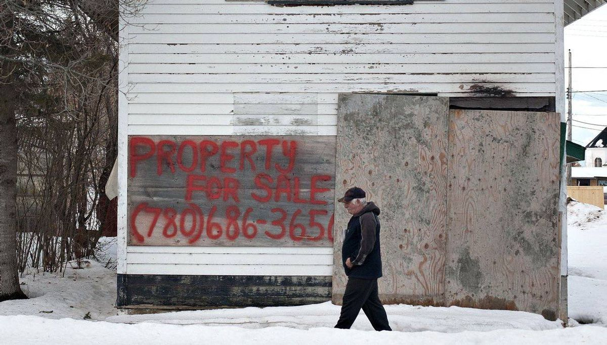 Chipman resident Nathan Harris walks past a boarded-up house that is for sale.
